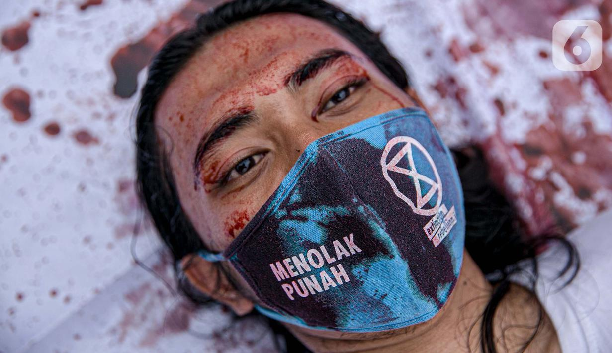 Aktivis melakukan teatrikal dengan menyiramkan darah di tubuhnya saat aksi serentak desak Presiden Jokowi deklarasikan Darurat Iklim di kawasan Patung Kuda, Jakarta, Jumat (19/3/2021). Aksi ini sebagai simbol banyaknya bencana yang terjadi di Indonesia. (Liputan6.com/Faizal Fanani)