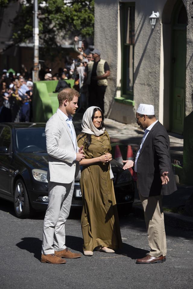 Meghan Markle mengenakan kerudung saat mengunjung masjid tertua di Afrika Selatan bersama Pangeran Harry. (DAVID HARRISON / AFP)