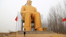 Seorang pria berada dibawah patung Presiden pertama Cina, Mao Zedong saat proses penyelesaian pembangunannya di ladang Desa Tongxu, Henan, Cina (4/1). Menurut warga, patung tersebut menghabiskan sekitar USD 460.000 atau Rp 6,4 miliar. (Reuters/Stringer)