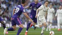 Gelandang Real Madrid, Luka Modric, berusaha melewati pemain Celta Vigo pada laga La Liga 2019 di Stadion Santiago Bernabeu, Sabtu (16/3). Real Madrid menang 2-0 atas Celta Vigo. (AP/Paul White)
