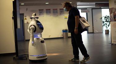 Seorang pria melihat pada robot yang dapat mendeteksi suhu dan masker di rumah sakit Universitas UZA di Antwerpen, Belgia pada 29 Mei 2020. Perusahaan Belgia, ZoraBots, menguji robot yang disebut CRUZR tersebut sebelum digunakan dalam beberapa minggu mendatang. (AP/Francisco Seco)