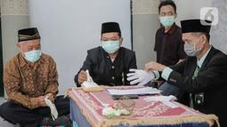 Penghulu mengenakan sarung tangan sebelum memimpin prosesi akad nikah di kawasan Pancoran, Jakarta, Rabu (1/4/2020). Sepasang pegantin menggelar pernikahan yang hanya dihadiri pihak keluarga guna menghindari pertemuan  orang banyak dan meminimalkan penyebaran COVID-19. (Liputan6.com/Faizal Fanani)