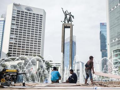Sejumlah pekerja menyelesaikan pembuatan panggung HUT ke-492 DKI di area Bundaran HI, Jakarta, Kamis (20/6/2019). Panggung megah tersebut nantinya akan digunakan sebagai area pesta rakyat. (Liputan6.com/Faizal Fanani)