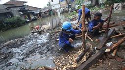 Pekerja menyelesaikan pembuatan tanggul darurat di kawasan Jatipadang, Jakarta, Rabu (22/11). Akibat banjir ini, warga yang terdampak semalam diungsikan sementara ke sebuah masjid di dekat lokasi. (Liputan6.com/Immanuel Antonius)