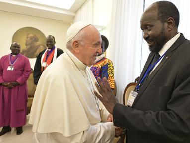 Paus Fransiskus berjabat tangan dengan Presiden Sudan Selatan, Salva Kiir dalam pertemuan dengan pemimpin Sudan Selatan di Vatikan, Kamis (11/4). Dalam pertemuan itu, Paus Fransiskus mencium kaki baik pejabat pemerintah maupun oposisi untuk menjaga perdam