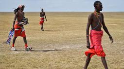 Suku Maasai membawa peralatannya untuk mengikuti pertandingan amal kriket di kaki Gunung Kenya (18/6). Mereka juga berusaha menggalang dana untuk penelitian yang berguna untuk menyelamatkan spesies badak putih. (AFP Phoo/Tony Karumba)