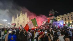 Pendukung Italia merayakan kemenangan di depan Katedral Duomo, Milan pada Senin (12/07/2021), setelah Italia berhasil mengalahkan Inggris pada Final Euro 2020 yang berlangsung di Stadion Wembley, London. Italia mengalahkan Inggris 3-2 dalam adu penalti setelah bermain imbang 1-1. (AP/Luca Bruno)