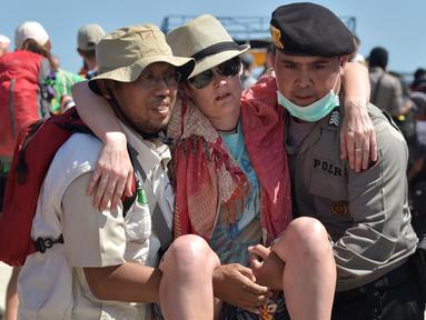 Petugas kepolisian dan penyelamat membantu turis asing yang dievakuasi dari Gili Trawangan saat tiba di Pelabuhan Bangsal, Lombok Utara, NTB, Selasa (7/8). Ribuan turis asing dievakuasi dari Gili Trawangan setelah gempa Lombok. (ADEK BERRY/AFP)