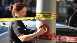 Petugas wanita memasang garis polisi di sekitar restoran cepat saji, di Hollywood, California setelah aksi penyerangan dengan pisau, Selasa (31/1). Sebelumnya, seorang pria melakukan penusukan membabi-buta di jalan dan pengunjung restoran (Robyn Beck/AFP)