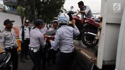 Petugas Dishub DKI mengangkut sepeda motor yang parkir sembarangan saat operasi penertiban di kawasan Pasar Tanah Abang, Jakarta, Senin (21/5). Razia pada hari kelima puasa itu untuk menertibkan parkir liar selama Ramadan. (Liputan6.com/Arya Manggala)