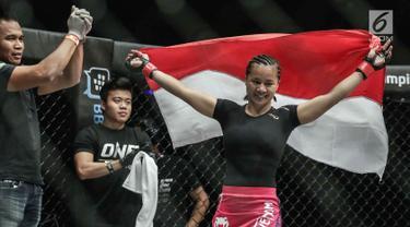 Petarung putri Indonesia, Priscilla Hertati Lumban Gaol membawa bendera merah putih usai mengalahkan petarung putri Malaysia, Audreylaura Boniface saat berlaga pada partai pertama One Championship di Jakarta, Sabtu (20/1). (Liputan6.com/Faizal Fanani)