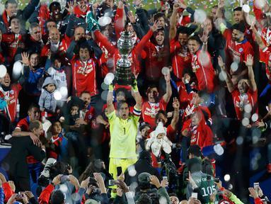 Kiper Chili, Claudio Bravo mengangkat trofi usai mengalahkan Argentina saat Final Copa America 2015  di Stadion Nasional, Santiago, Chili, (4/7/2015). Chili menang lewat adu penalti atas Argentina dengan skor 4-1. (REUTERS/Ueslei Marcelino)