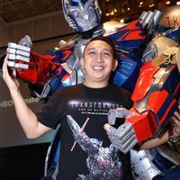 Augie Fantinus ceria berpose bersama Optimus Prime, salah satu tokoh Transformers (Galih W Satria/Bintang.com)