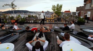 Penonton berendam dalam bak mandi sambil menyaksikan penyanyi opera Adam Plachetka membawakan Don Giovanni karya Mozart di atap Gedung Lucerna, Praha, Republik Ceko, Kamis (29/8/2019). (AP Photo/Petr David Josek)