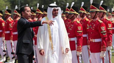 Presiden Joko Widodo (Jokowi)  bersama Putra Mahkota Abu Dhabi, Sheikh Mohamed Bin Zayed Al Nahyan memeriksa pasukan saat kunjungan kenegaraan di Istana Bogor, Kamis (24/7/2019). Keduanya menggelar pertemuan bilateral guna membahas sejumlah kerja sama. (Willy Kurniawan/Pool Photo via AP)