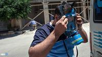 Seorang petugas penyelamat korban perang mengenakan masker gas kimia. (AFP/Daniel Leal-Olivas/wwn)