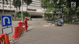 Petugas mengalihkan pengendara sepeda motor yang akan melintasi proyek pembangunan jalur kereta Light Rail Transit (LRT) di Jalan Setiabudi Tengah, Jakarta, Senin (17/6/2019). Jalan Setiabudi Tengah ditutup mulai 17 Juni 2019 hingga 20 Februari 2020. (Liputan6.com/Herman Zakharia)
