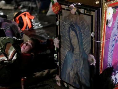 Seorang peziarah beristirahat di samping gambar Bunda dari Guadalupe di kawasan Basilika Guadalupe di Mexico City, Meksiko (11/12). Bunda dari Guadalupe dikenal juga dengan sebutan Our Lady of Guadalupe atau Virgin of Guadalupe. (Reuters/Henry Romero)
