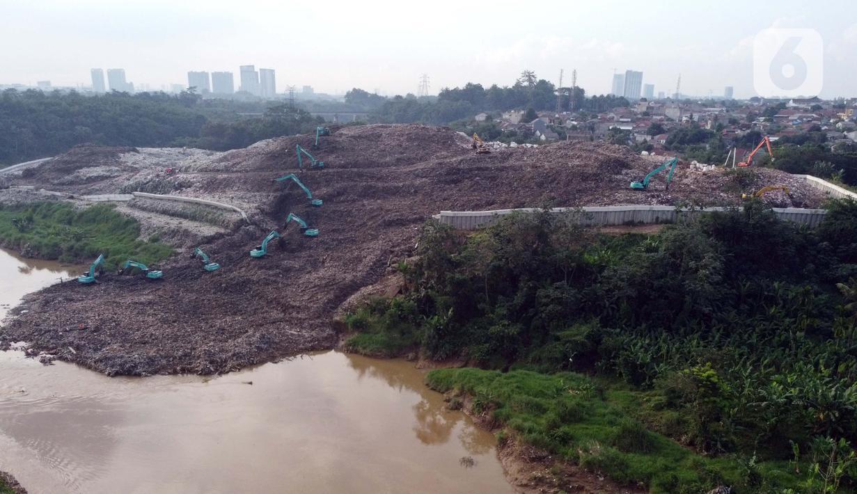 Foto udara memperlihatkan alat berat memindahkan tumpukan sampah dari Tempat Pembuangan Akhir (TPA) Cipeucang yang masuk ke area Sungai Cisadane, Serpong, Tangerang Selatan, Rabu (3/6/2020). Sebelumnya, pada Jumat (22/5/) lalu turap yang menopang TPA tersebut jebol. (Liputan6.com/Helmi Fithriansyah)