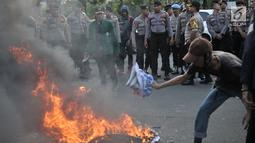 Mahasiswa gabungan se-Jabodetabek membakar ban bekas saat menggelar aksi unjuk rasa di depan Istana Merdeka, Jakarta, Selasa (16/7/2019). Dalam aksi ini sempat terjadi aksi saling dorong dengan pihak kepolisian. (merdeka.com/Iqbal S. Nugroho)