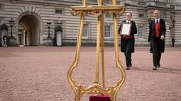Senior footman Olivia Smith dan Heather McDonald saat akan memajang pengumuman kelahiran bayi baru kerajaan di halaman depan Istana Buckingham, London, Inggris, Senin (23/4). Anak ketiga Kate Middleton berjenis kelamin laki-laki. (Pool Photo via AP)