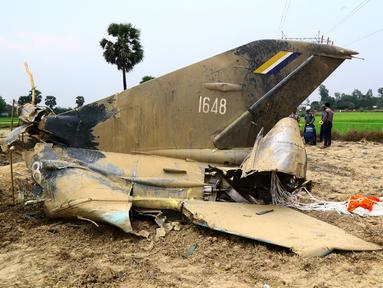Reruntuhan jet tempur milik Myanmar jatuh di area persawahan desa Kyunkone yang berjarak satu jam dari ibu kota Naypyidaw, Selasa (3/4). Pilot pesawat jet tempur tersebut tewas karena lukanya saat dalam perjalanan ke rumah sakit militer. (AFP Photo)