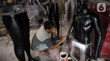 Seorang pekerja menyelesaikan pembuatan maneken di Kebon Jeruk, Jakarta Barat, Senin (28/12/2020). Maneken yang terbuat dari bahan viber tersebut dijual dengan harga Rp 1 juta. (merdeka.com/Dwi Narwoko)