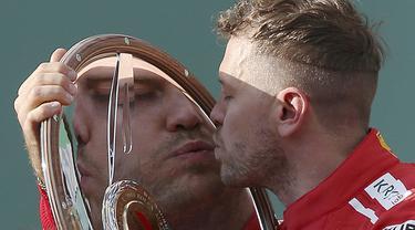 Pebalap Ferrari, Sebastian Vettel mencium trofi usai memenangi balapan F1 GP Australia di Sirkuit Albert Park, Melbourne, Minggu (25/3/2018). Vettel memenangi balapan dengan selisih 5,036 detik dari Hamilton. (AP/Rick Rycroft)
