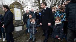 Presiden Prancis Emmanuel Macron berjalan melewati makam Yahudi yang dicoret simbol Nazi di pemakaman Yahudi, Quatzenheim, Prancis, Selasa (19/2). Macron menyempatkan diri untuk memeriksa kerusakan yang ditimbulkan. (Frederick FLORIN/AFP)