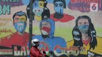 Seorang pengendara motor melewati mural anjuran kebiasan hidup baru dengan 3 M di Stasiun Cawang, Jakarta, Sabtu (26/12/2020). Pemerintah terus berupaya melakukan imbauan kepada warga untuk melaksanakan kebiasaan baru 3M guna memutus penyebaran virus corona (COVID-19). (merdeka.com/Imam Buhori)