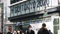 Orang-orang yang mengenakan masker berjalan dekat papan bertema Olimpiade yang disponsori perusahaan sekuritas di Tokyo, Jepang, Jumat (29/1/2021). Olimpiade 2020 Tokyo yang ditunda terkait pandemi virus corona Covid-19 dijadwalkan ulang untuk diadakan pada musim panas ini. (AP Photo/Hiro Komae)