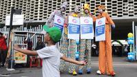 Tiga seniman egrang membawa poster Kampanye Aman Untuk Anak pada acara Deklarasi Pemilu Ramah Anakdi Gedung Bawaslu, Jakarta, Minggu (17/3). KPU melarang anak-anak untuk terlibat dalam aktivitas kampanye politik.(Liputan6.com/Herman Zakharia)