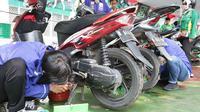 Montir menservis dan ganti oli motor milik buruh secara gratis di Lapangan Ahmad Yani, Tangerang, banten (1/5). Lebih 500 sepeda motor medapatkan servis dan ganti oli secara gratis oleh Serikat Pekerja Seleruh Indonesia. (Merdeka.com/Arie Basuki)