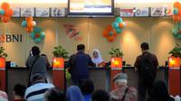 Teller melayani nasabah dan memberikan bunga mawar dan souvenir kepada nasabah di Kantor Cabang BNI Tebet, Jakarta (5/7). Kegiatan tersebut merupakan rangkaian HUT ke 72 BNI. (Merdeka.com/Arie Basuki)