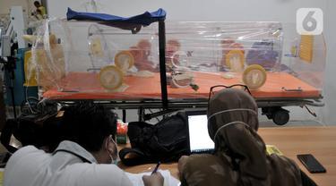 Petugas menyiapkan alat pendukung perawatan pasien virus corona COVID-19 di Rumah Sakit Darurat Penanganan COVID-19 di Wisma Atlet Kemayoran, Jakarta, Minggu (22/3/2020). RS Darurat Penanganan COVID-19 hampir 100 persen rampung. (merdeka.com/Iqbal S. Nugroho)