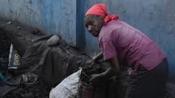 Seorang wanita mengumpulkan arang di depot yang akan dijualnya di pasar lokal, di Les Cayes, Haiti, (25/1). Peraturan tersebut untuk melindungi zona pemotongan kayu. (AP/David McFadden)