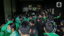 Sejumlah pengemudi ojek online berkerumun saat antre mengambil pesanan di gerai cepat saji McDonald's Raden Saleh, Jakarta, Rabu (9/6/2021). Puluhan driver ojek online terlihat mengabaikan protokol kesehatan saat mengantre pesanan BTS Meal yang mulai dijual. (Liputan6.com/Faizal Fanani)
