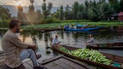 Seorang pria Kashmir menyaksikan orang lain menjual produk mereka di pasar sayur terapung di Danau Dal di Srinagar, Kashmir yang dikuasai India pada 26 Juli 2020. Sayuran yang diperdagangkan di pasar terapung ini disuplai ke Srinagar dan banyak kota di lembah Kashmir. (AP Photo/Dar Yasin)
