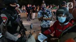 Polisi memeriksa dokumen pengendara yang melintas di posko penyekatan mudik di Kedungwaringin, Kabupaten Bekasi, Senin (10/5/2021). Pada H-3 menjelang Idul Fitri 1442 H, jumlah petugas yang berjaga di pos penyekatan pemudik di Kedungwaringin ditambah sebanyak 150 orang (Liputan6.com/Herman Zakharia)