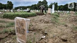 Petugas saat merapikan salah satu makam jenazah terkait Covid-19 di TPU Tegal Alur, Jakarta, Kamis (14/1/2021). Kepala Satuan Pelaksana TPU Tegal Alur Wawan Wahyudi mengungkapkan blok pemakaman muslim khusus jenazah terpapar Covid-19 telah penuh. (merdeka.com/Iqbal S. Nugroho)