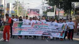 Peserta membawa spanduk mengikuti kegiatan Millenial Road Safety Festival Gorontalo, Minggu (10/2). Kegiatan dilaksanakan sebagai upaya memberikan pengetahuan kalangan millenial di Gorontalo untuk tertib berlalulintas.(Liputan6.com/Rahmad Arfandi Ibrahim)