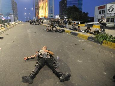 Anggota Dalmas BKO dari Polda Bali beristirahat usai mengamankan perusuh di atas fly over Slipi, Jakarta, Rabu (22/5/2019). Bentrokan panjang dengan para perusuh membuat anggota kepolisian yang berhadapan langsung kurang beristirahat. (merdeka.com/Arie Basuki)