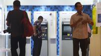 Pengunjung melakukan penarikan uang melalui ATM di kawasan Jakarta, Jumat (25/1). Sepanjang 2018, volume transaksi debit Mandiri tumbuh 6% secara year on year (yoy), sedangkan dari sisi nominalnya tumbuh 7% yoy. (Liputan6.com/Angga Yuniar)