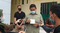 Kasi Intel Kantor Imigrasi Kelas I TPI Gorontalo Budi Mangatjo saat menunjukan dokumen resmi WNA Afsel (Arfandi Ibrahim/Liputan6.com)