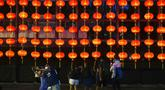 Orang-orang foto di depan dekorasi selama Festival Pertengahan Musim Gugur di taman Victoria di Hong Kong, Selasa (21/9/2021).  Festival ini jatuh pada hari ke-15 bulan ke-8 penanggalan Imlek. (AP Photo/Vincent Yu)