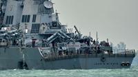 Petugas mengecek Lambung kiri kapal perang USS John S. McCain usai tabrakan dengan kapal tanker Alnic MC berbendera Liberia di Selat Malaka, sebelah timur Singapura, (21/8). (AFP Photo/Roslan Rahman)