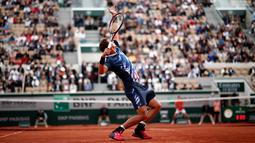 Petenis Swiss, Henri Laaksonen memukul bola ke arah lawannya petenis Serbia, Novak Djokovic pada putaran kedua Prancis Terbuka 2019 di Stadion Rolland Garros, Kamis (30/5/2019). Novac Djokovic berhasil melaju ke babak ketiga setelah mengandaskan Henri Laaksonen 6-1, 6-4 6-3. (REUTERS/Benoit Tessier)