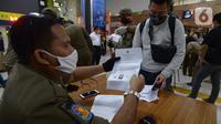 Petugas mengecek SIKM milik penumpang di stasiun Gambir Jakarta, Kamis (28/5/2020). Penumpang yang mudik dari Surabaya mengunakan kereta api luar biasa harus memiliki SIKM sebagai syarat yang dimiliki warga untuk keluar atau masuk ke wilayah Jakarta. (merdeka.com/Imam Buhori)