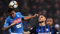 Gelandang Napoli, Allan melompat untuk merebut bola dari pemain Inter Milan Mauro Emanuel Icardi dalam lanjutan Serie A di Giuseppe Meazza, Senin (12/3). Inter Milan  dan Napoli harus puas berbagi angka dengan skor akhir 0-0. (MARCO BERTORELLO / AFP)