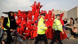 Aktivis lingkungan berdiri di atas halte bus saat melakukan blokade Jembatan Waterloo, London, Inggris (17/4). Aksi blokade ini untuk mendorong pemerintah berbuat lebih dalam mengatasi perubahan iklim yang terjadi. (AFP Photo/Tolga Akmen)